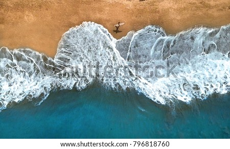 AERIAL, TOP DOWN: Unrecognizable surfer walking along the exotic sandy beach on sunny summer day. Lonely man holding surfboard looking at splashing ocean waves. Splashing ocean waves reach sandy beach #796818760