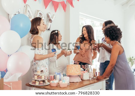 Pregnant woman celebrating baby shower party with female friends at home. Group of multi-ethnic women at a baby shower. Royalty-Free Stock Photo #796828330