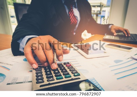 A businessman analyzing investment charts at his workplace and using his laptop and touch calculator. #796872907