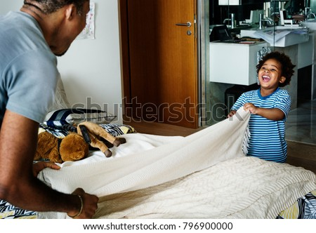 Dad and son changing bed sheet together #796900000