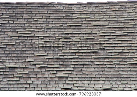 wood shingle roof in poor repair. Wood shingles are thin, tapered pieces of wood primarily used to cover roofs and walls of buildings to protect them from the weather. susceptible to fire and costly #796923037