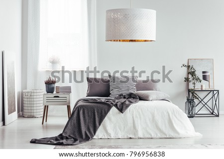 White lamp in bright bedroom interior with heather and books on nightstand and patterned bedding on the bed #796956838