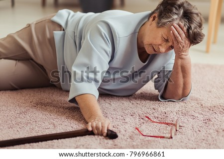 Sick senior woman with headache lying on the floor after falling down Royalty-Free Stock Photo #796966861