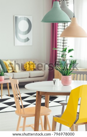 Close-up of colorful lamps hanging above round dining table in bright, open space apartment interior #796978000