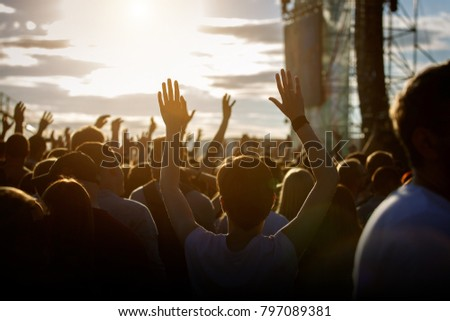 Teenagers at summer music festival enjoying themselves, raised hands, sunset #797089381