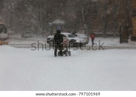 ODESSA, UKRAINE-January 16, 2018: Strong snowfall, cyclone in city streets in winter. Cars are covered with snow. Slippery road. Bad weather in winter: heavy snow and snowstorm. Pedestrians go on snow #797101969