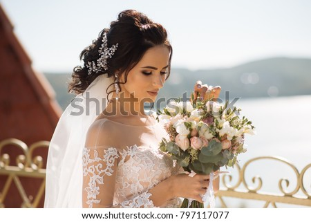 Beautiful bride with wedding flowers bouquet, attractive woman in wedding dress. Happy newlywed woman. Bride with wedding makeup and hairstyle. Smiling bride. Wedding day. Gorgeous bride. Marriage. #797117077
