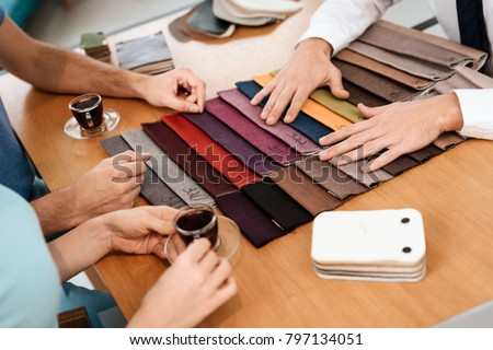 The seller shows samples of materials for furniture. A young couple came to a furniture store. #797134051