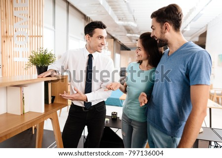The furniture store manager demonstrates furniture to the buyers. A guy and a girl are listening with a good mood to the seller. #797136004