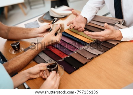 The seller shows samples of materials for furniture. A young couple came to a furniture store. #797136136