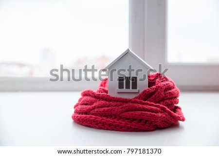 house in winter - heating system concept and cold snowy weather with model of a house wearing a knitted cap #797181370