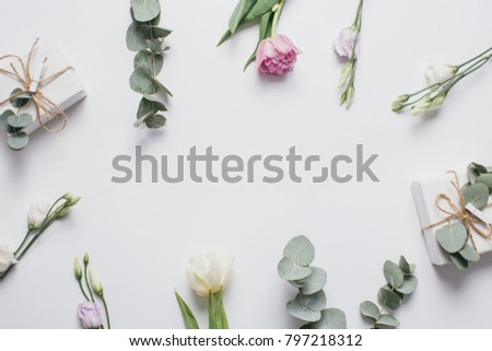 Mother's Day Composition: Eustoma, Eucalyptus and a gift box on a white background. Top view.Flat lay. #797218312
