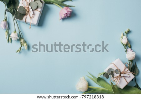Mother's Day Composition: Eustoma, eucalyptus, tulips and a gift boxes on a blue background. Top view.Flat lay. #797218318