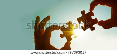 two hands of businessman to connect couple puzzle piece with sky background.Jigsaw alone wooden puzzle against sun rays.one part of whole.symbol of association and connection.business strategy #797393017