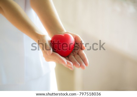 Nursing women Snug red heart heart in hand with love and care with which will very as well; #797518036