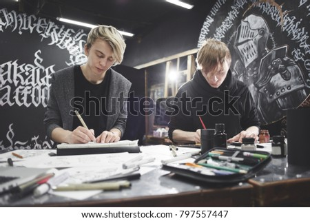 Portrait of the masters of calligraphy. Tattoo artists make a sketch sitting at the table in the Studio. This working process #797557447