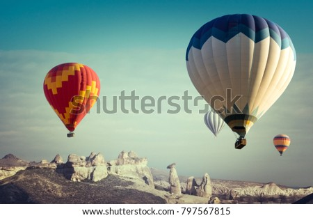 Colorful hot air balloons flying above the mountain landscape of Cappadocia. Romantic travel on modern aerostat or fantastic background for adventure in steampunk style. #797567815
