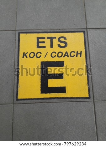 Signage of coach E for electric train service painted on the floor  #797629234