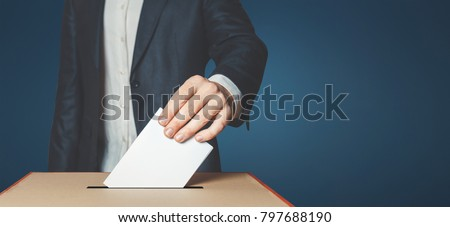 Man Voter Putting Ballot Into Voting box. Democracy Freedom Concept Near Blue Wall Copy-Space #797688190