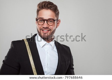 Handsome young tailor with tape measure on shoulder wearing suit and glasses.  #797688646