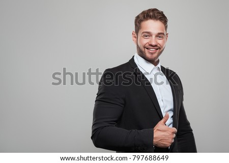 Handsome young muscular man showing thumb up gesture on gray background.  #797688649