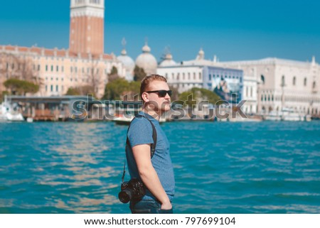 Man with camera and sunglasses standing on the background of Venice and the blue sea #797699104