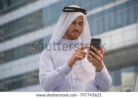 Middle Eastern Emirati Man in traditional clothing called kandura checking his mobile. #797743621