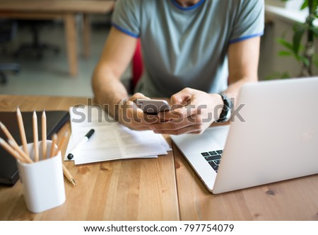 Man successful marketing specialist checking e-mail on mobile phone during work on laptop computer in co-working. Male project or content manager chatting on cellphone after webinar on modern net-book Royalty-Free Stock Photo #797754079