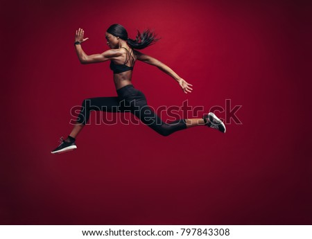 Female athlete running and jumping. Side view shot of healthy african woman working out against red background. Royalty-Free Stock Photo #797843308