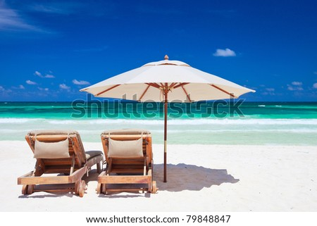 Two chairs and umbrella on stunning tropical beach in Tulum, Mexico #79848847