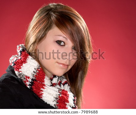Teenaged girl wearing a winter scarf and bold eye make-up giving a challenging glance to the viewer. Red background. #7989688