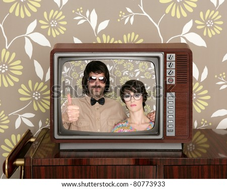 old wooden tv with nerd silly couple retro in screen on wallpaper background [Photo Illustration]