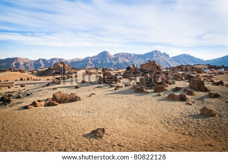A spot in Tenerife with many rocks and a beautiful mountain landscape in the background #80822128