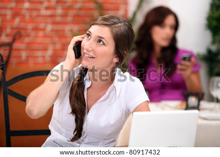 Young woman on a mobile in a restaurant #80917432