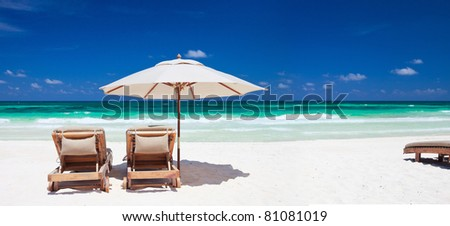 Two chairs and umbrella on stunning tropical beach in Tulum, Mexico #81081019