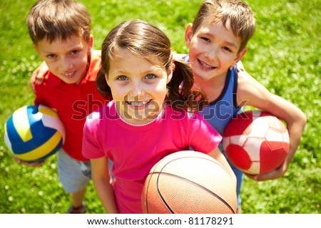Portrait of three little children with balls looking at camera and smiling Royalty-Free Stock Photo #81178291