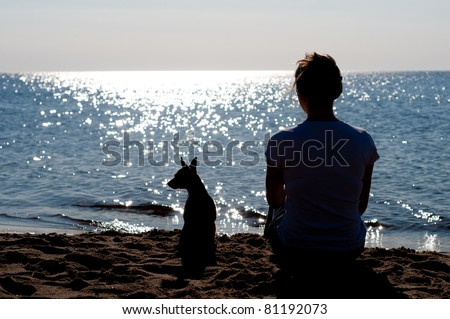 Girl silhouette sitting on the beach with a small dog #81192073