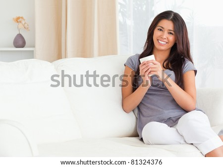 charming woman with cup looking into camera in living room #81324376