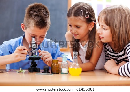 Eminent elementary school boy looking into microscope while girls are watching #81455881