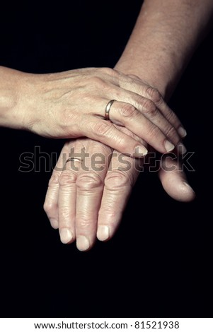 Hands of two loving senior people on a dark background #81521938