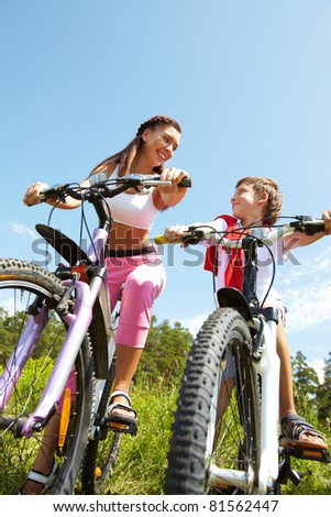 Mother and son sitting on bikes and looking at each other #81562447