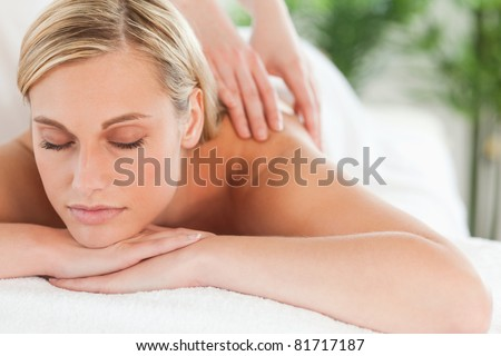 Close up of a smiling woman relaxing with eyes closed on a lounger during a massage in a wellness center