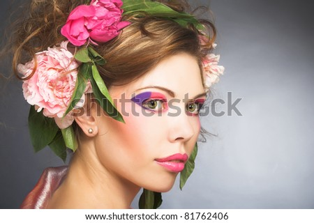 Portrait of young charming woman with artistic make-up and with flowers in her hair #81762406