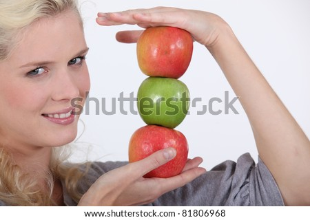 young blonde holding pile of apples #81806968