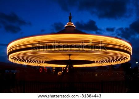 Carousel (merry-go-round) time lapse photo shot in late evening light at a carnival. #81884443