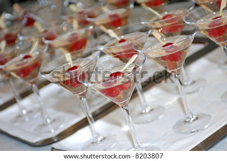 Lines of glasses filled with champagne and two raspberries on a stick, photographed with a shallow depth of field #8203807