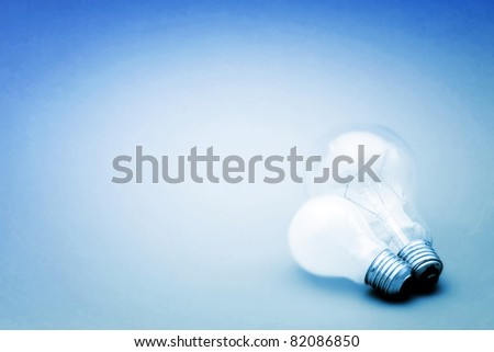 Background with lit lightbulb. Isolated on blue #82086850