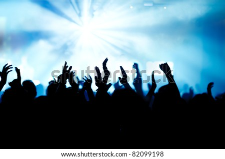 silhouettes of concert crowd in front of bright stage lights #82099198