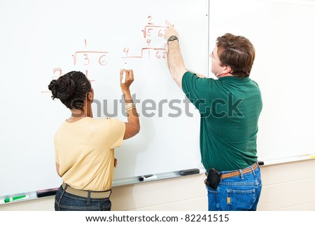 High school student and teacher at the white board doing long division.  Focus on the equations. #82241515