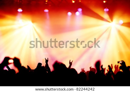 silhouettes of concert crowd in front of bright stage lights #82244242